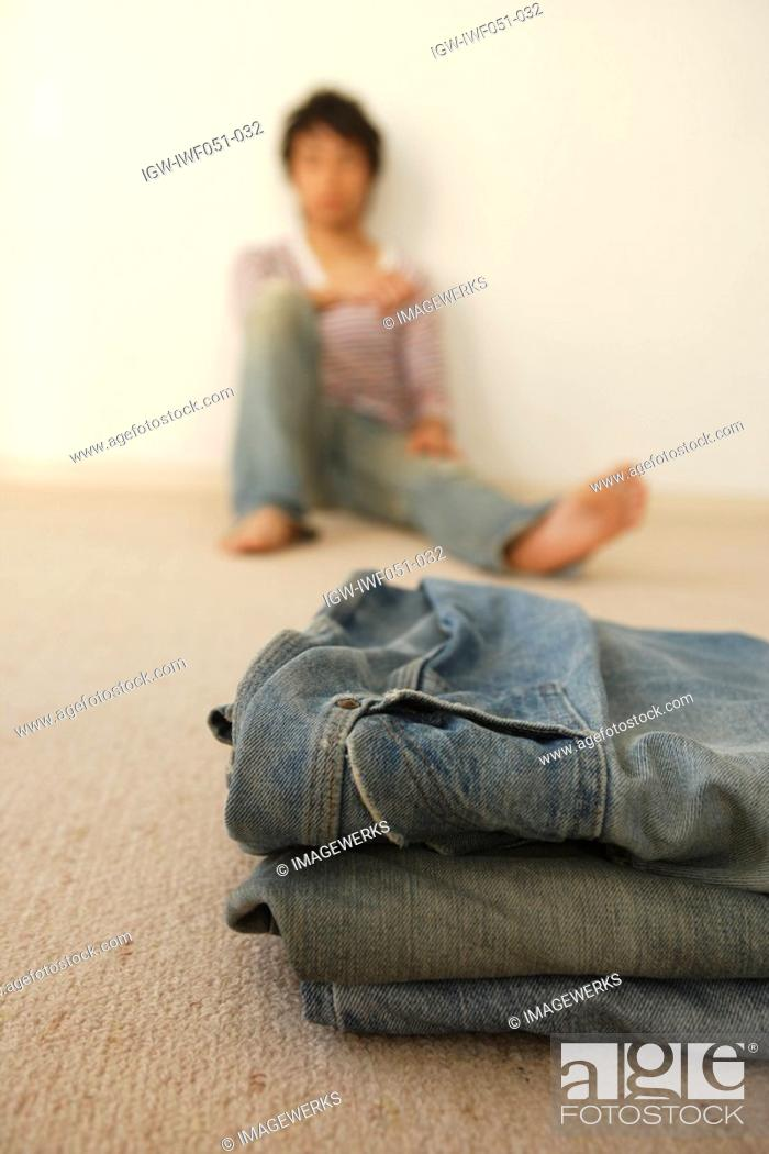 Stock Photo: Young man sitting by wall while jeans on foreground.