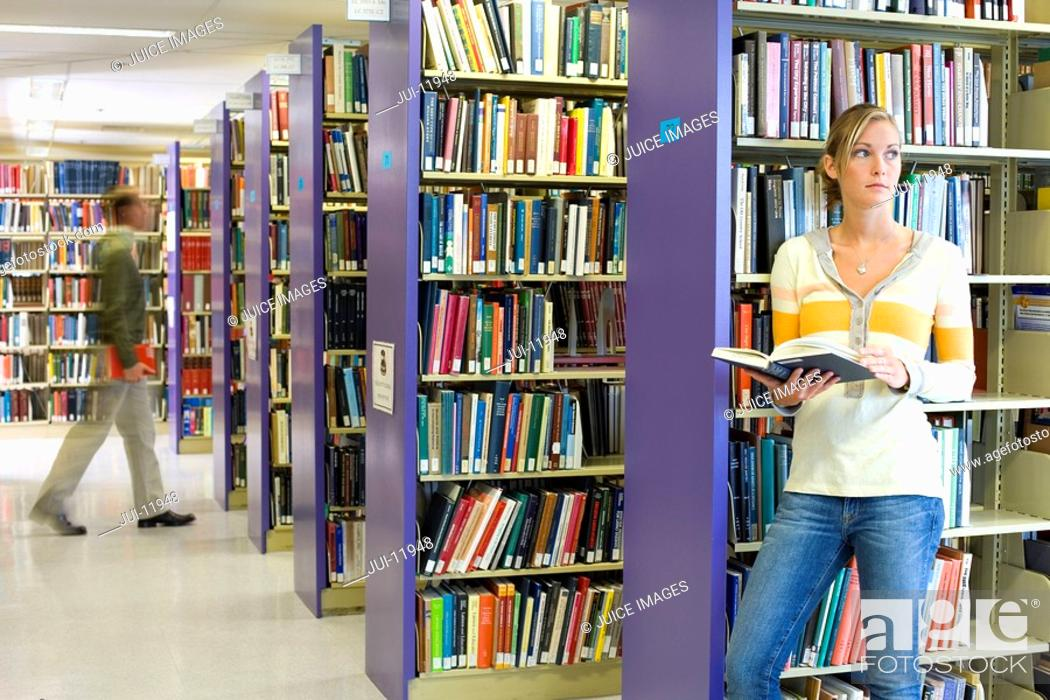 Stock Photo: Woman with book in library.