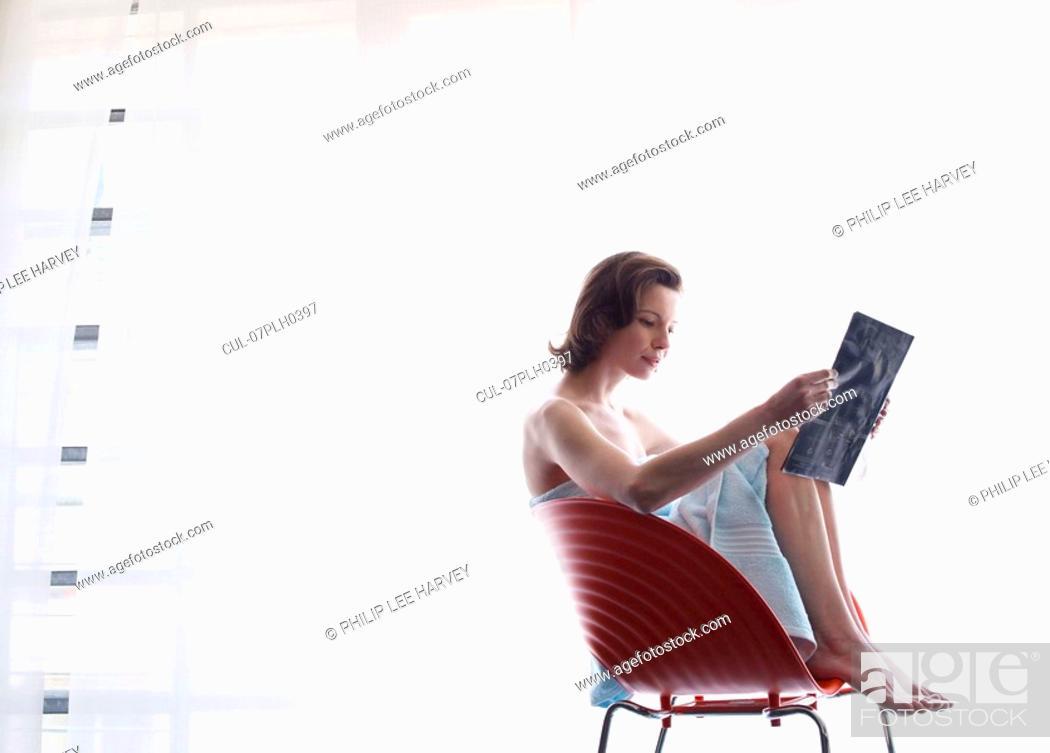 Stock Photo: Woman sitting at window reading.