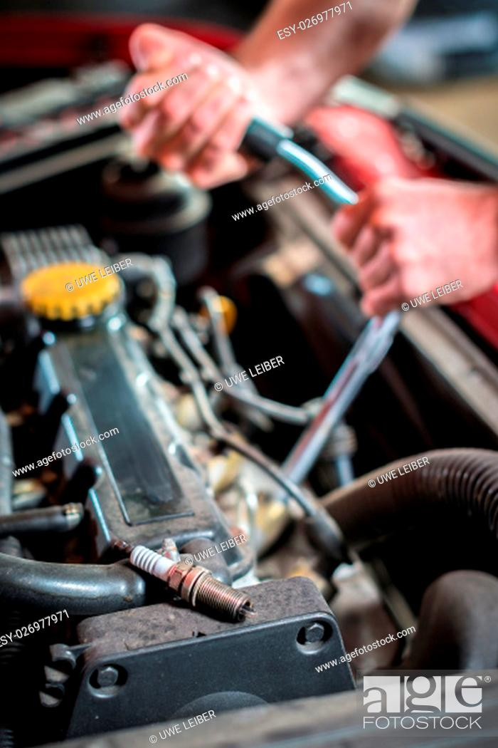 Stock Photo: Starting ignition plug in front of hands of a car mechanic in auto repair service, red automobile.