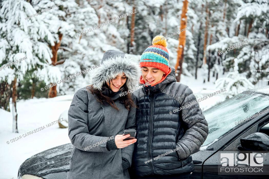 Stock Photo: Smiling young couple leaning at parked car in winter forest looking at cell phone.