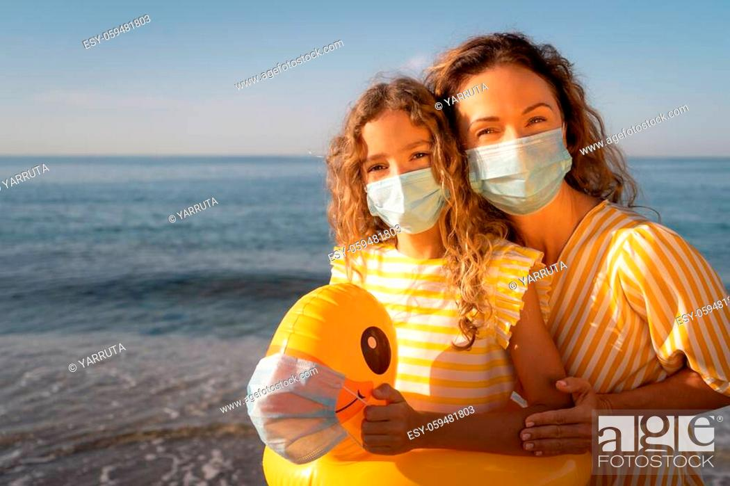 Stock Photo: Happy mother and daughter wearing medical mask outdoor against blue sky background. Woman and child enjoying by sea at summer.