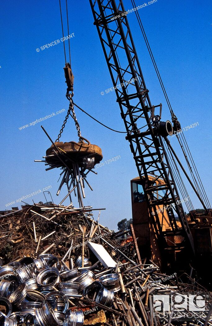 Stock Photo: A giant crane-mounted electromagnet is used to move a pile of iron and steel items at a scrap yard in Carson, California.