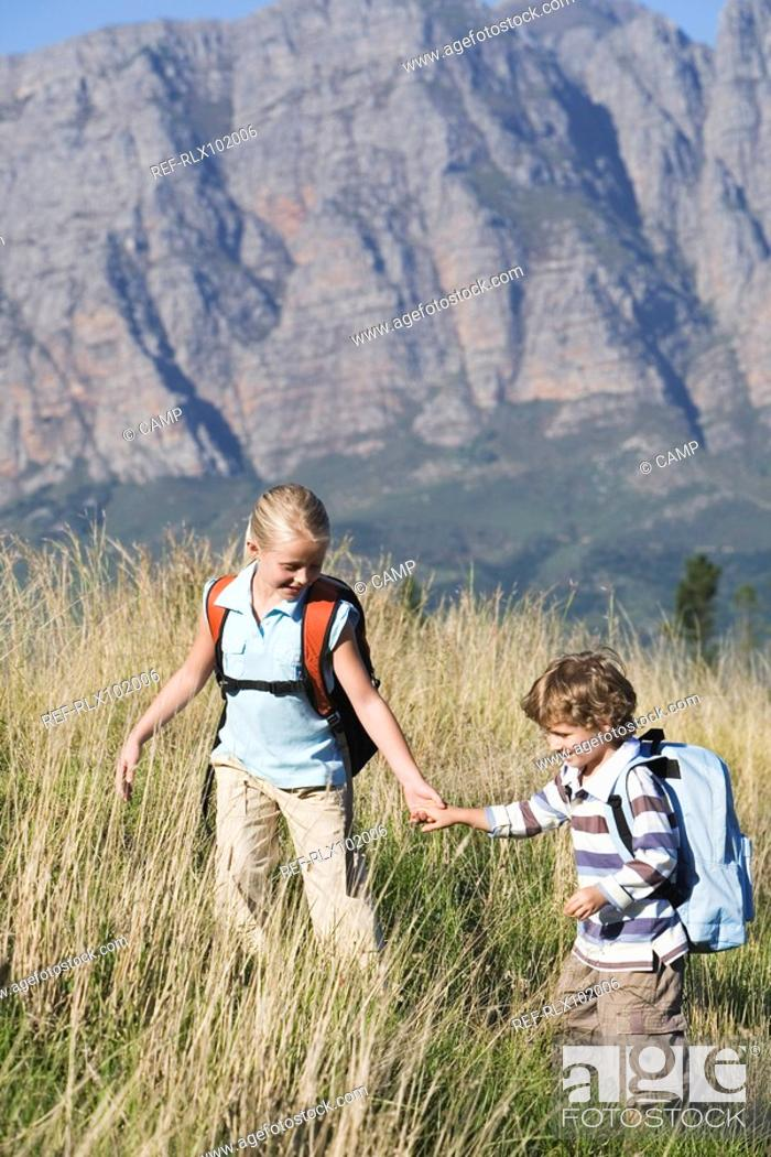 Stock Photo: Two children outdoors, hiking with backpack, mountains in background.