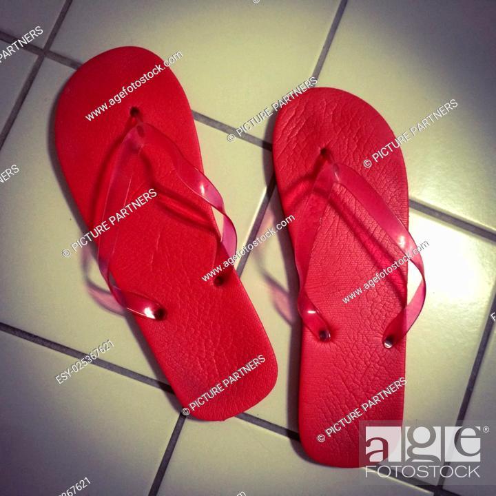 Photo de stock: Red bath flip flops on white tiles in the bathroom.