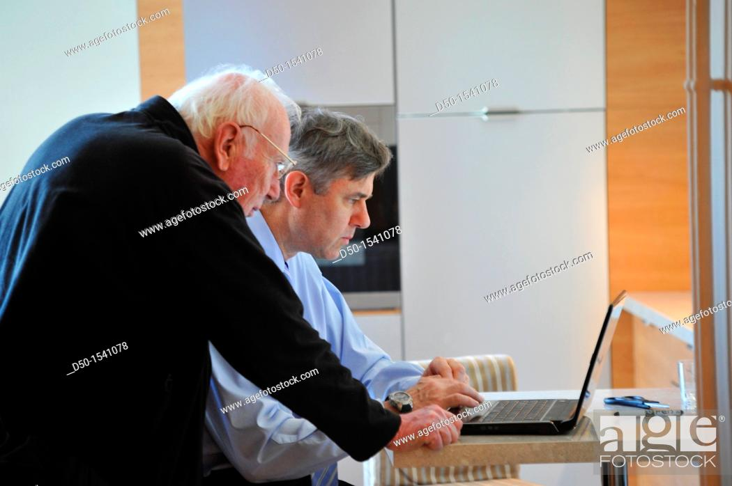 Imagen: Son helping father with computer, Paris, France.