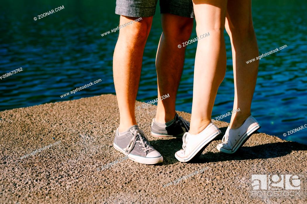 Stock Photo: Legs of a man and a woman in sneakers standing hugging each other on the pier close-up, a woman is standing on tiptoe . High quality photo.