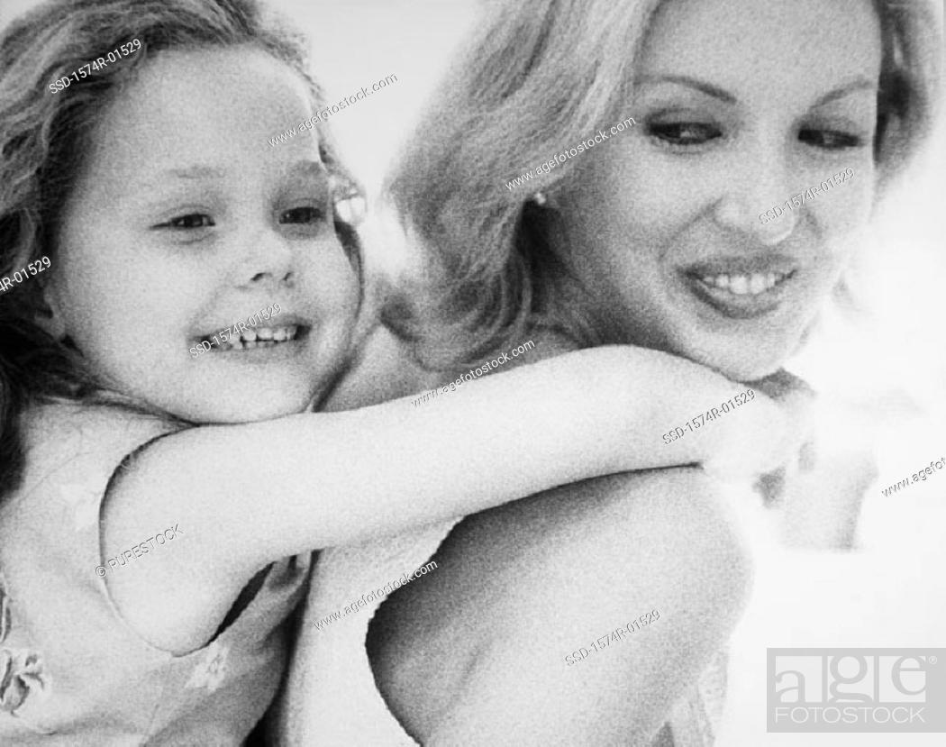 Stock Photo: Close-up of a young woman carrying her daughter on her back.