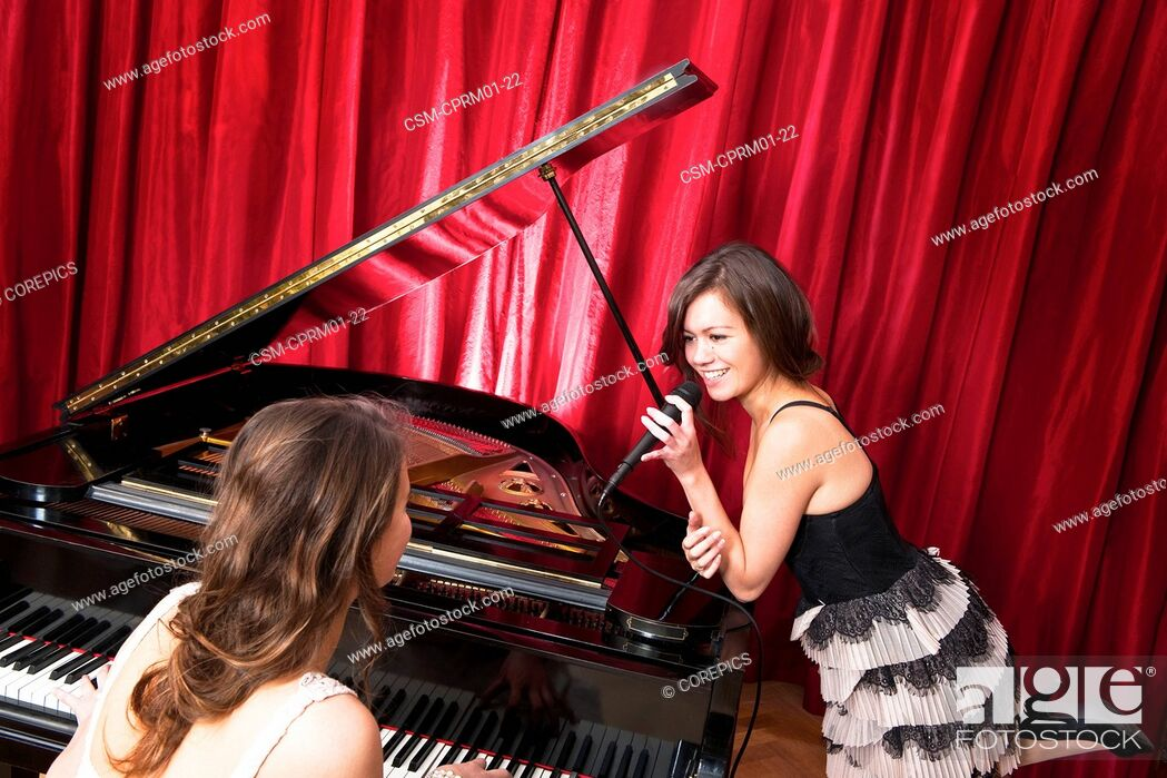 Photo de stock: Two women singing a duet with a concert piano, having fun together.