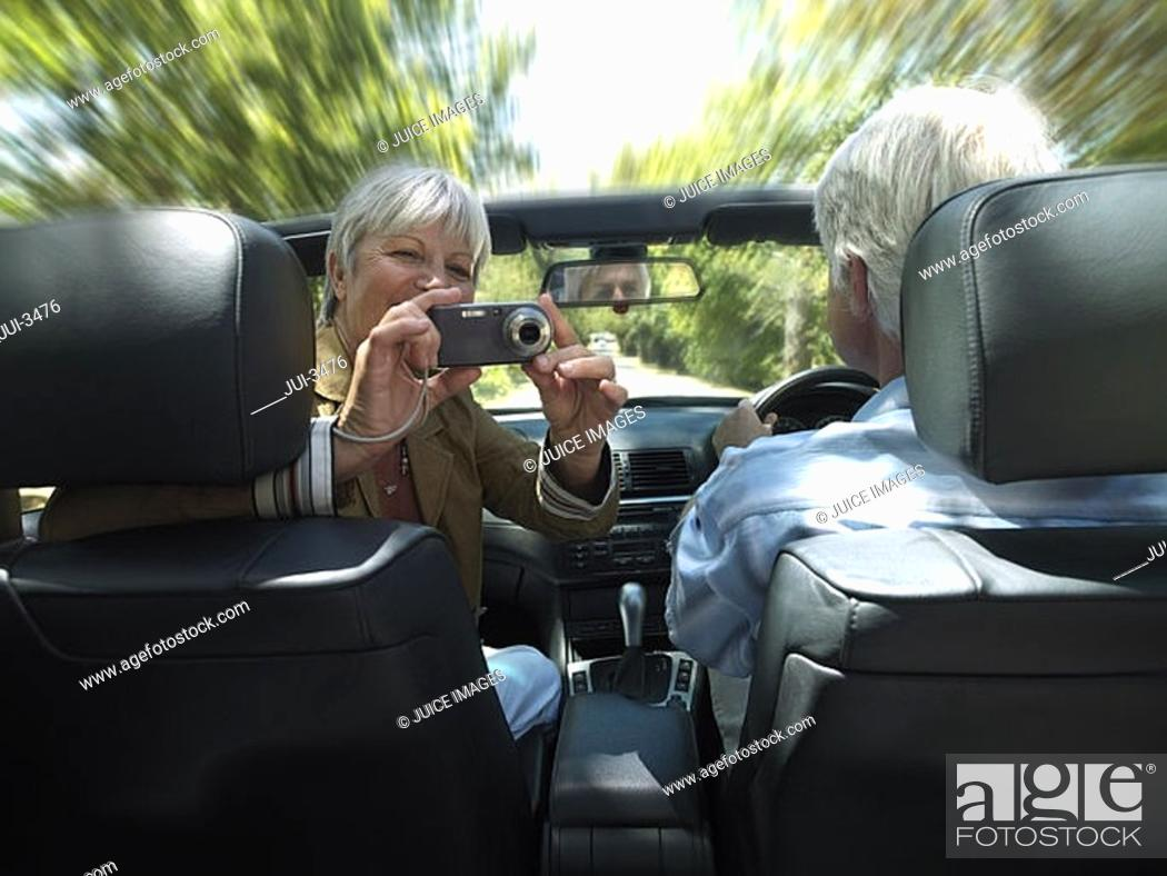 Stock Photo: Senior couple driving in convertible car along country road, woman taking photograph, rear view.