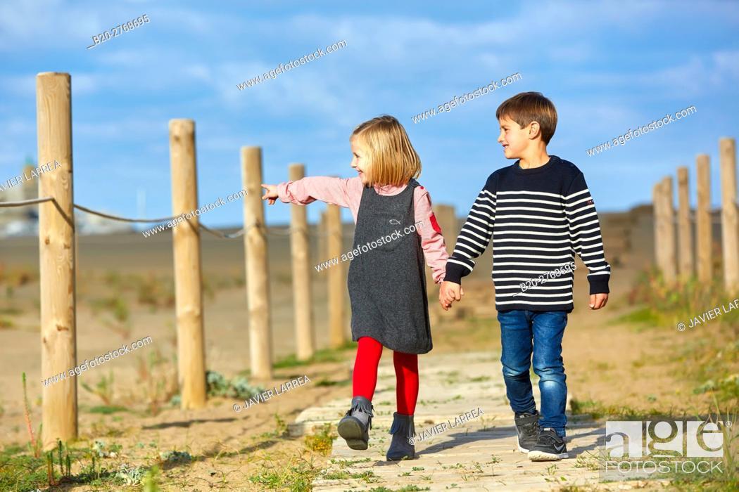 Stock Photo: Children walking on the beach, Zumaia, Gipuzkoa, Basque Country, Spain.