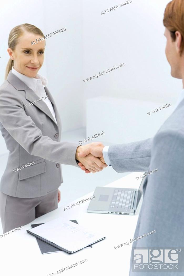 Stock Photo: Businesswoman shaking hands with cropped view of red-headed businessman.