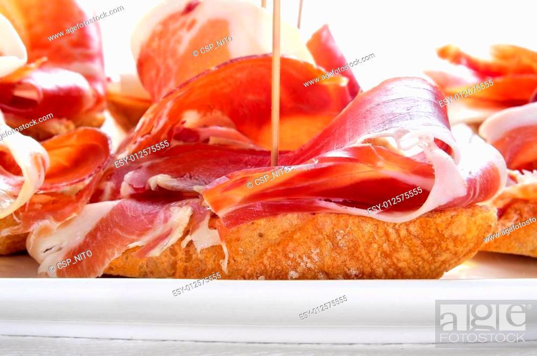 Imagen: spanish pinchos de jamon, serrano ham served on bread.