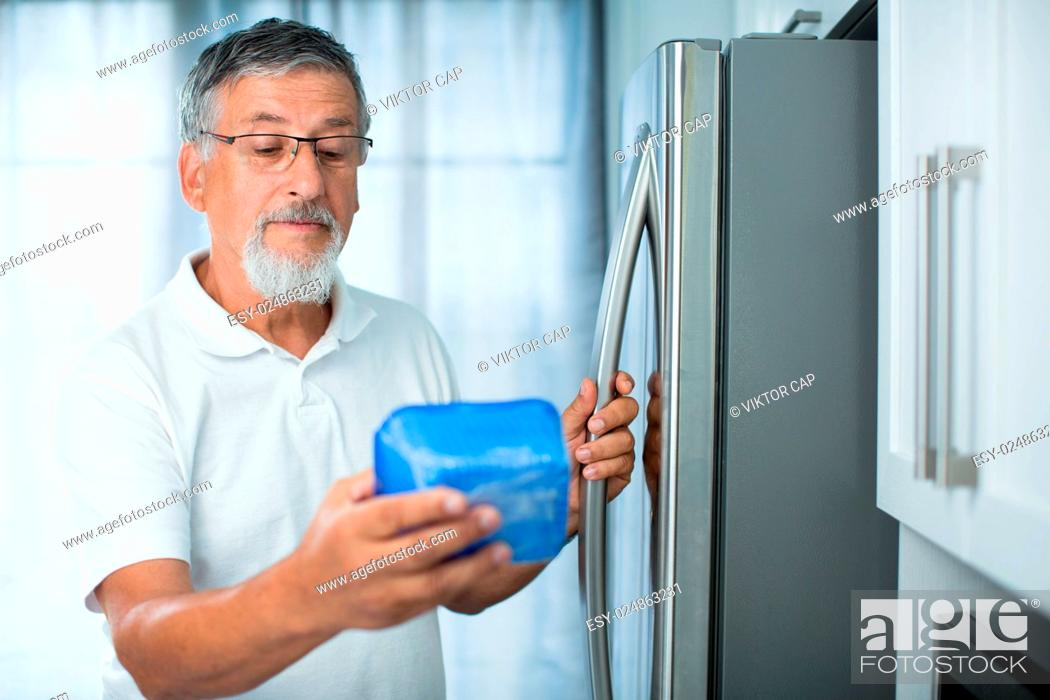 Stock Photo: Is this still fine? Senior man in his kitchen by the fridge, looking at the expiry date of a product she took from her fridge -.