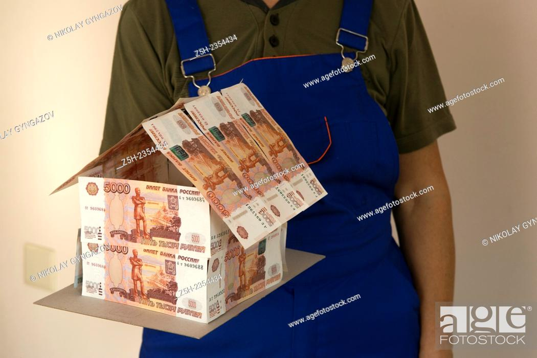 Stock Photo: Russian Federation. Builder with a model house of Russian money.