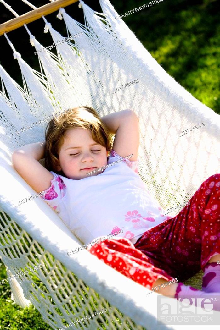 Stock Photo: Little girl sleeping on a hammock.