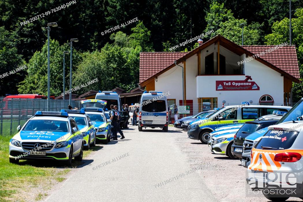 Stock Photo: 12 July 2020, Baden-Wuerttemberg, Oppenau: Police vehicles are parked at a meeting place near the community in front of a sports home.