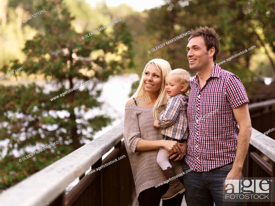 Stock Photo: Happy smiling young parents and a two year old girl enjoying the nature view from a bridge  Ontario, Canada.