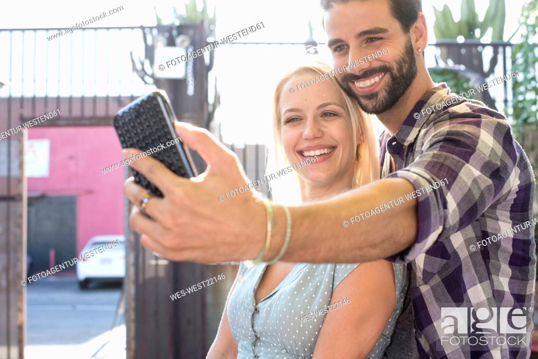Stock Photo: Happy young man with girlfriend taking a selfie.