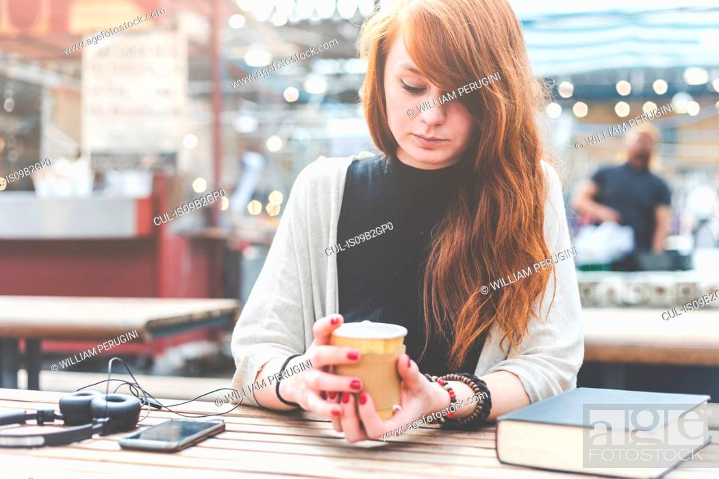 Stock Photo: Woman at pavement cafe holding disposable cup, London, UK.