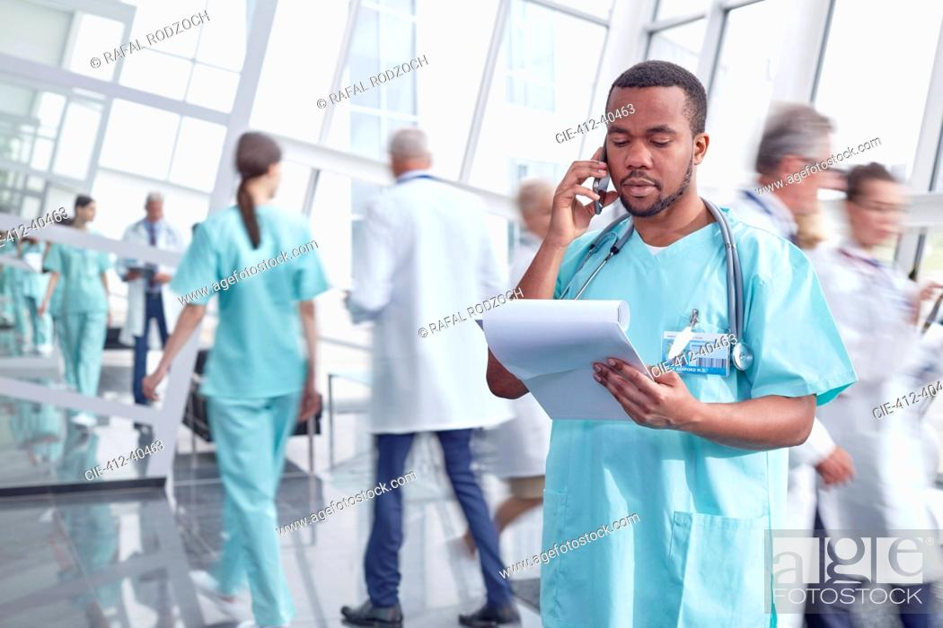 Photo de stock: Male surgeon with clipboard talking on cell phone in hospital lobby.