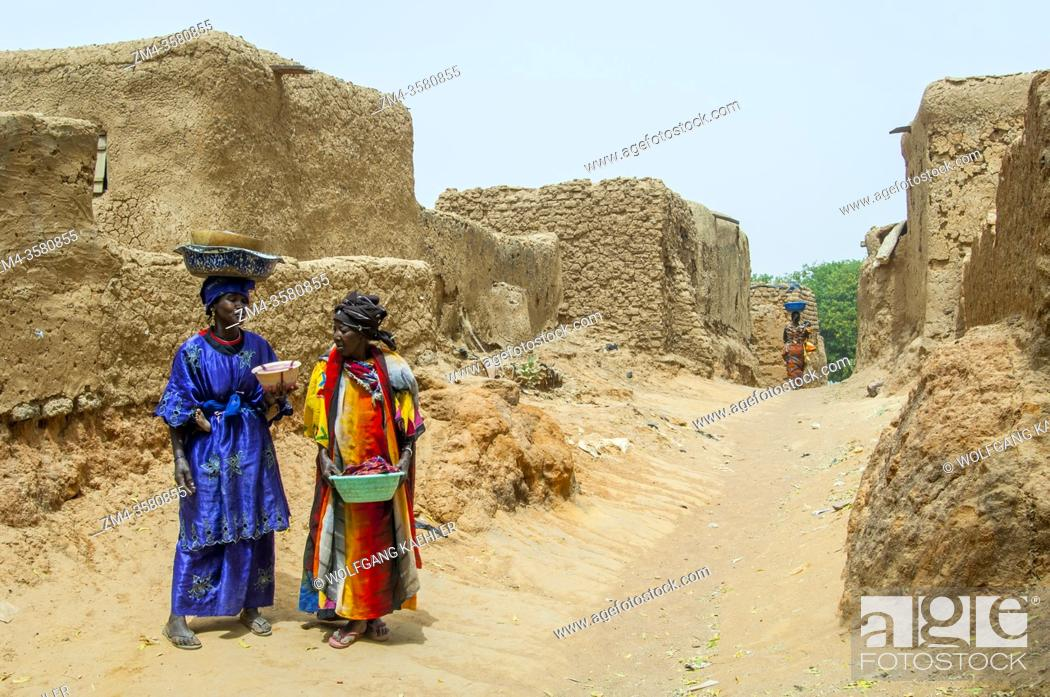 Stock Photo: Two women are walking through the Segoukoro village (Bambara tribe) near Segou city in the center of Mali, West Africa.
