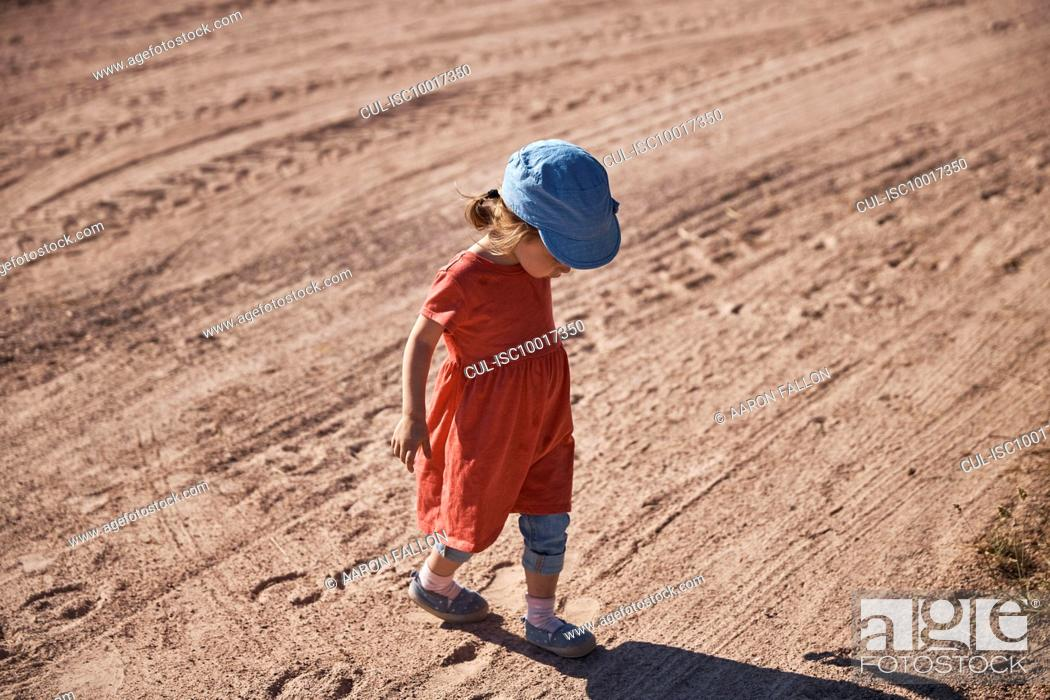 Stock Photo: Toddler looking at shadow on dirt road.