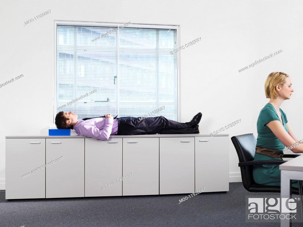 Stock Photo: Businessman sleeping on office cabinets near woman working.
