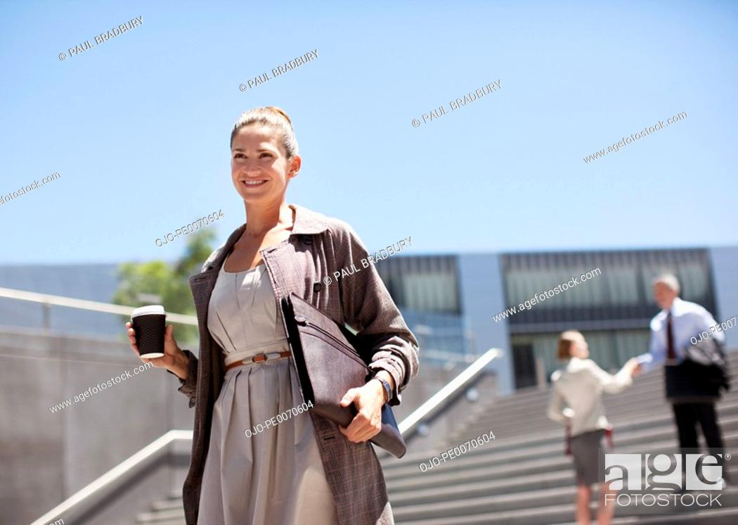 Stock Photo: Businesswoman with coffee walking down steps.