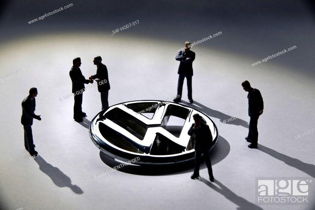 Imagen: Modellfiguren stehen um VW-Logo herum.