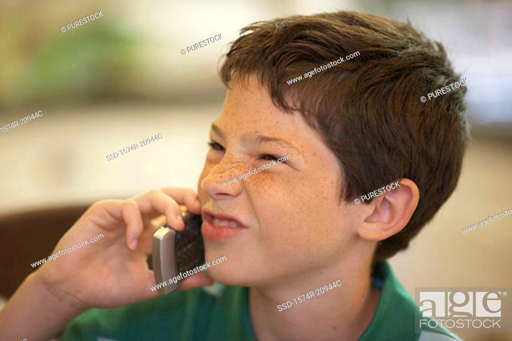 Stock Photo: Close-up of a boy using a mobile phone and making a face.