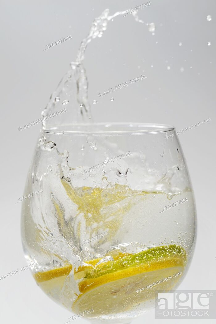 Stock Photo: Citrus fruits, lemon and lime slices splashing in a glass on white background.