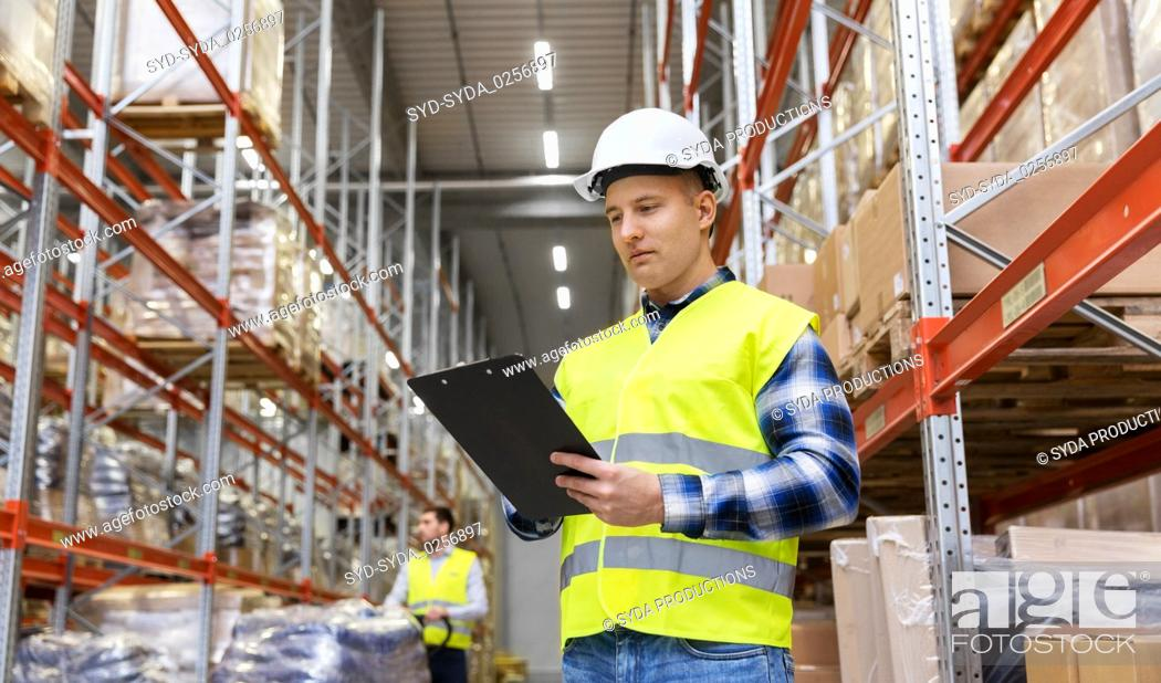 Stock Photo: warehouse worker with clipboard in safety vest.