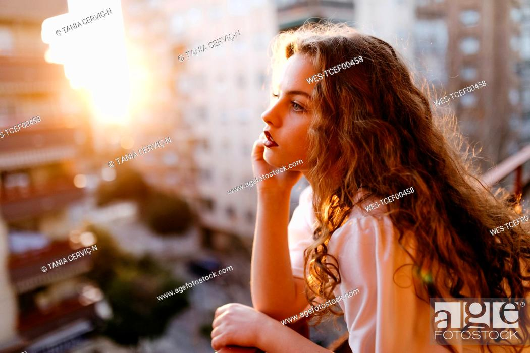 Stock Photo: Portrait of beautiful young woman on balcony at sunset.