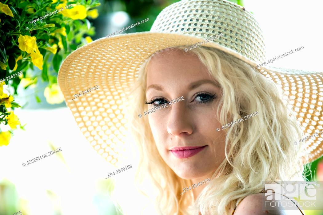 Stock Photo: A portrait of a pretty 30 year old blond woman wearing a straw hat smiling at the camera.