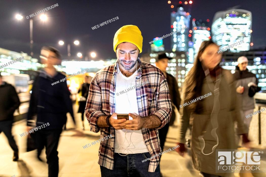Photo de stock: UK, London, smiling man looking at his phone by night with blurred people passing nearby.