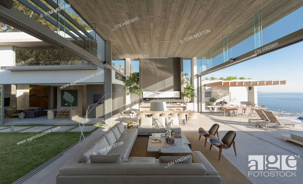 Stock Photo: Sunny, open modern, luxury home showcase interior living room with courtyard and ocean view.