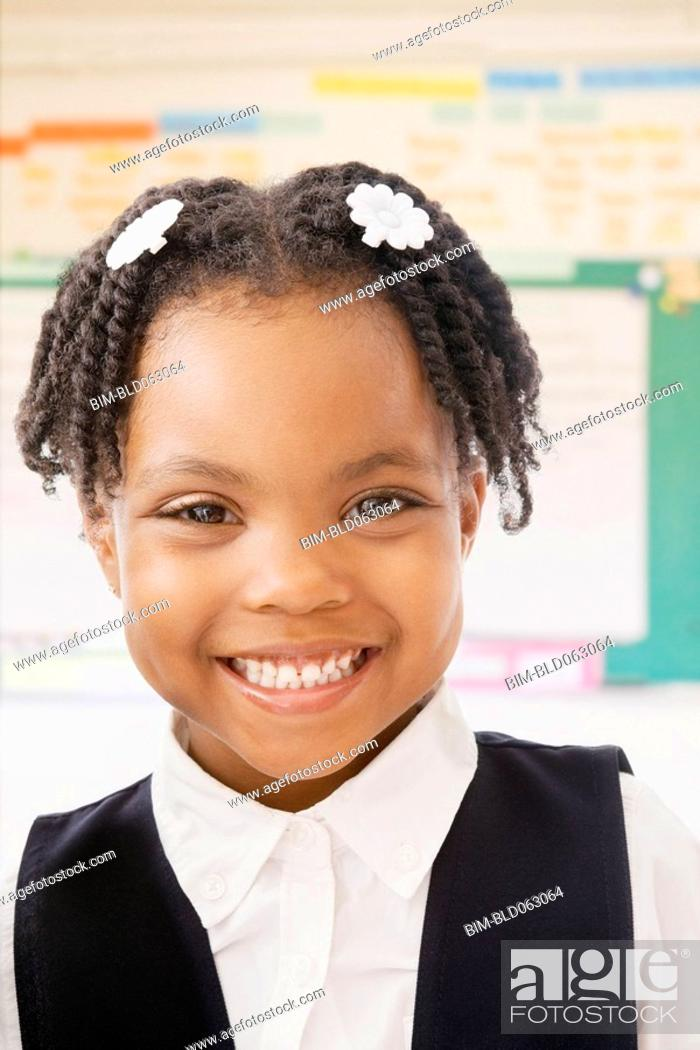 Stock Photo: African school girl smiling in classroom.
