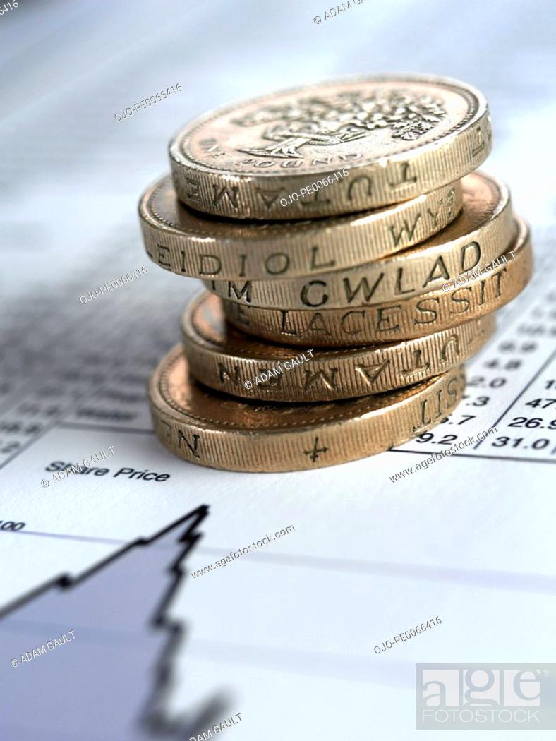 Stock Photo: Stack of British pound coins on list of share prices.
