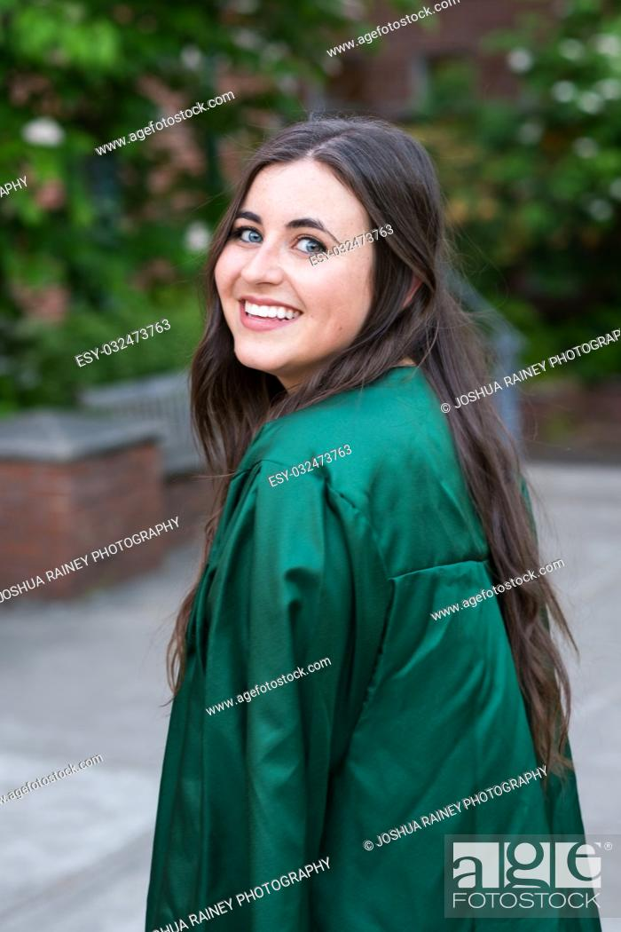 Stock Photo: Female college student in a natural light lifestyle portrait while wearing her graduation gown right before graduating from a university.