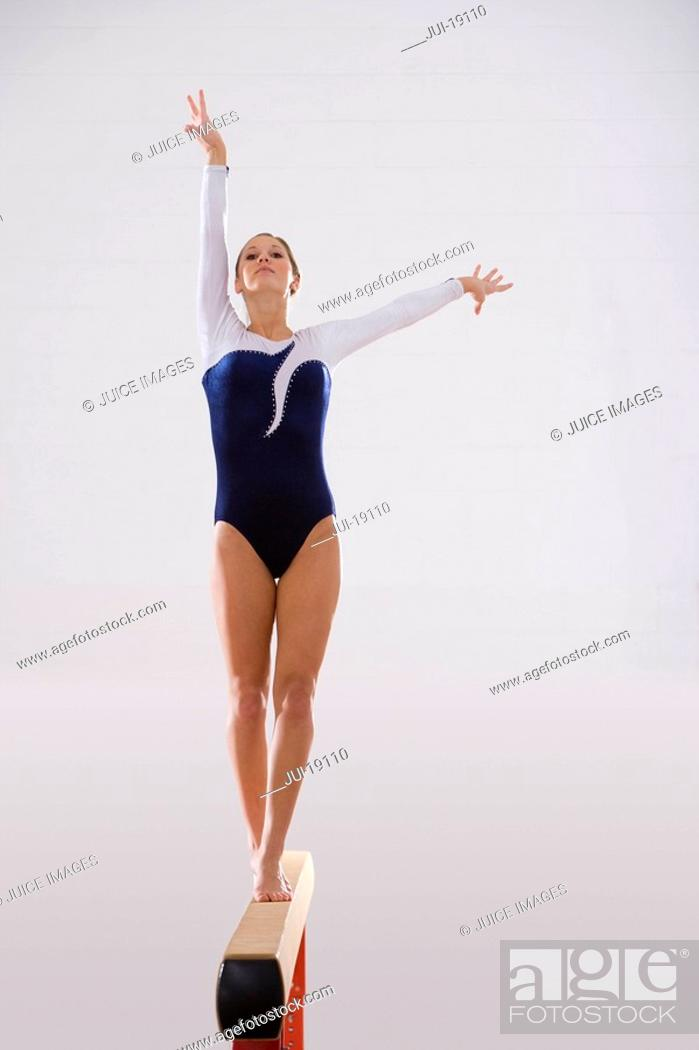 Stock Photo: Female gymnast performing on balance beam, portrait, low angle view.