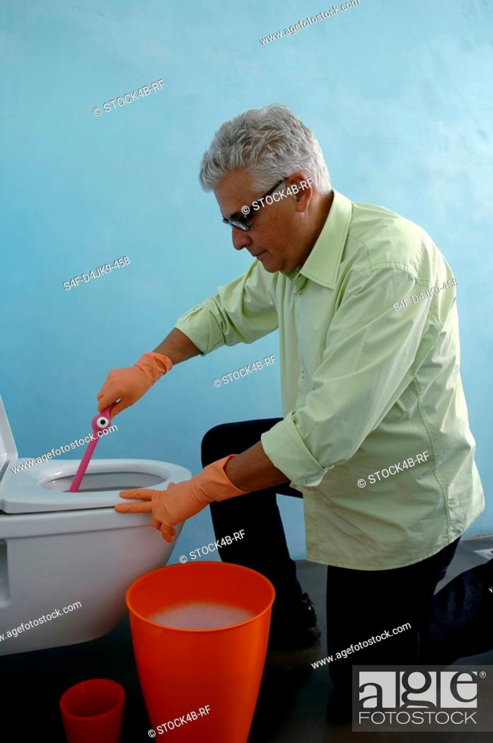 Stock Photo: Senior man cleaning the toilet with a brush.