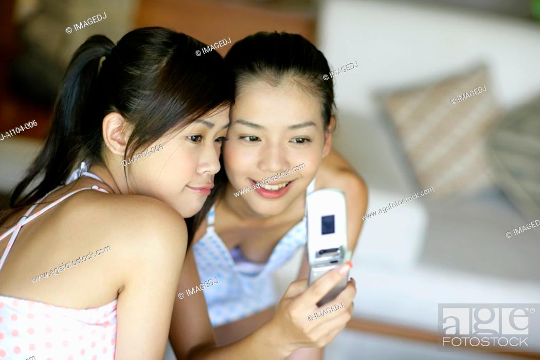 Stock Photo: Young women looking at mobile phone.