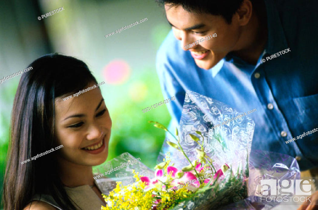 Stock Photo: Young man giving a bouquet to young woman.