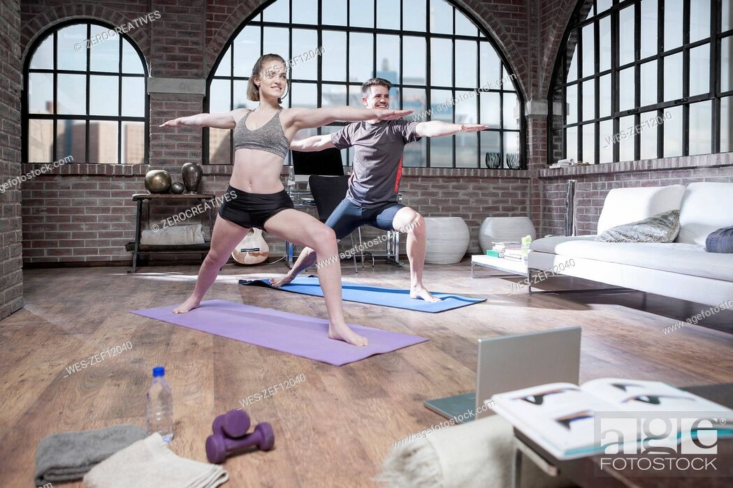 Stock Photo: Young man and woman doing yoga exercise in studio.