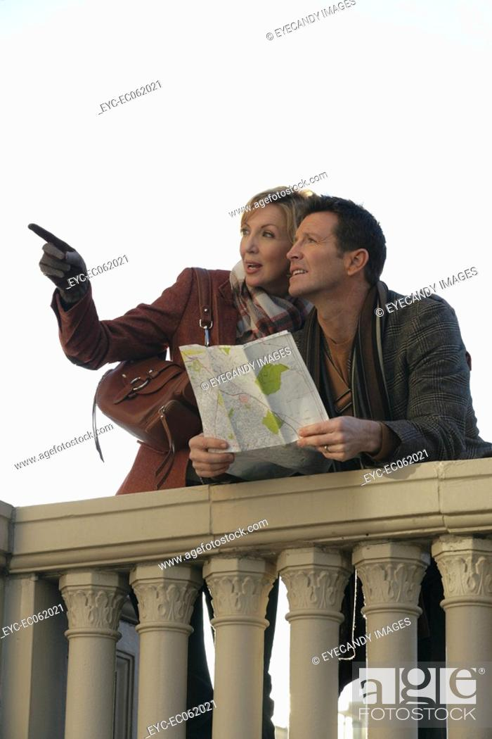 Stock Photo: Mature couple holding a map.