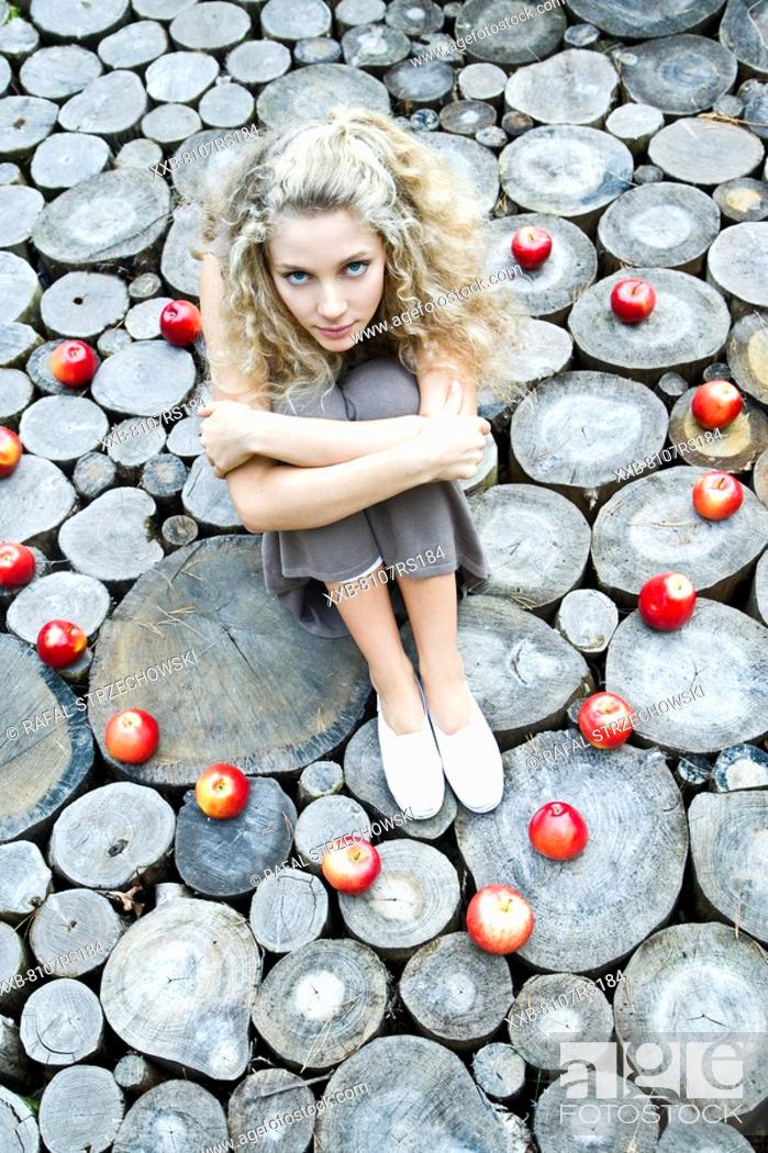 Stock Photo: Young woman sitting in apples ring.