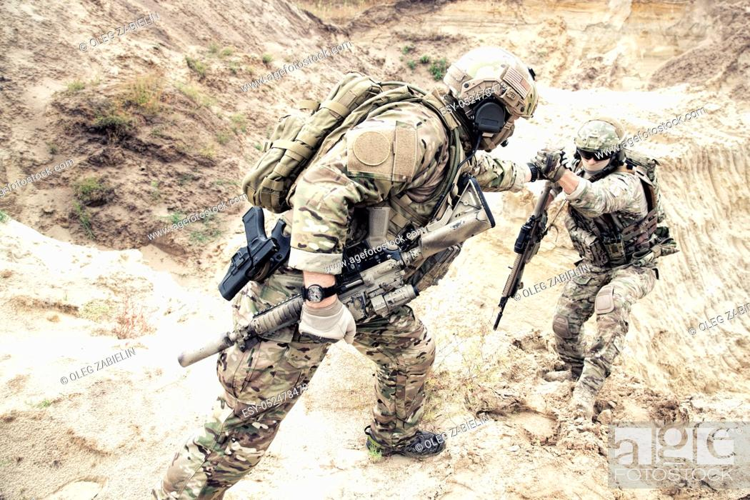 Imagen: US ranger, modern infantryman, special reconnaissance team member or military scout in ammunition, armed with service rifle helping brother in arms to climb on.