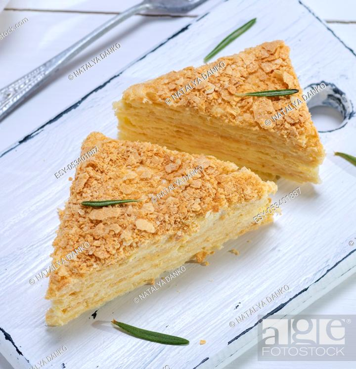 Stock Photo: baked cakes Napoleon with cream on a white wooden board, top view.
