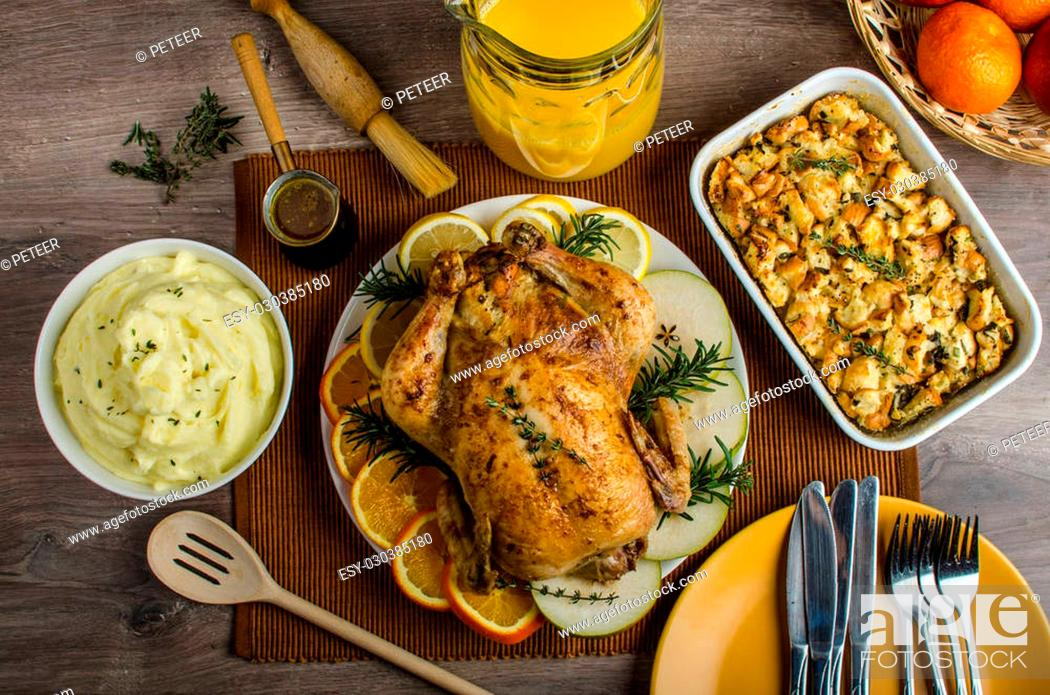 Stock Photo: Feasting - stuffed roast chicken with herbs, mashed potatoes with oregano leaves and homemade stuffing with herbs, freshly squeezed orange juice.